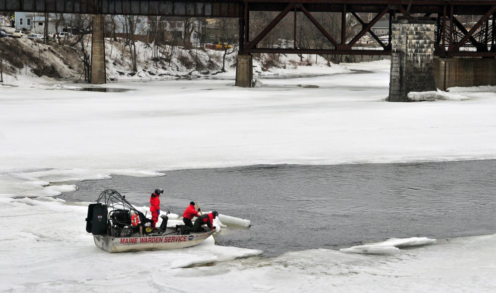 Wardens on an airboat search the Kennebec River for a woman who disappeared under the ice between the Calumet Bridge at Old Fort Western and the railroad trestle on Saturday in Augusta.