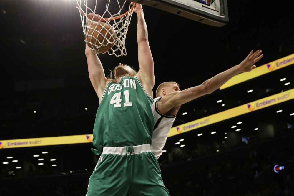 Boston Celtics center Kelly Olynyk dunks against Brooklyn Nets center Mason Plumlee during the second half of Monday night's win by the Celtics in Brooklyn.