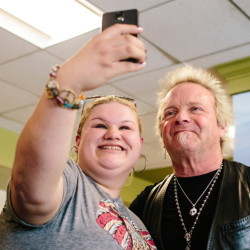 Autumn Johnson holds up her cellphone to take a selfie with Aerosmith drummer Joey Kramer during his visit to St. Joseph's College in Standish to promote his Rockin' & Roastin' coffee on Thursday.