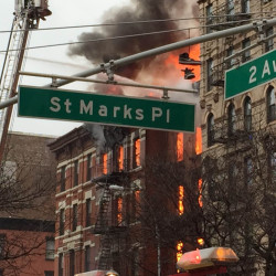New York City firefighters work to extinguish a large fire and a partial building collapse in the East Village neighborhood of New York on Thursday.