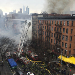Smoke rises from a burning building in New York's East Village on Thursday. Firefighters said at least 12 people were hurt, and flames were spreading to other buildings.