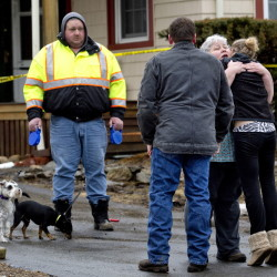 Diana Tullos receives a hug from her daughter, Jess Griffin, at right, as Diana's husband, Rodger, looks on with their two dogs, Sister and Lil' Bit, after the Tullos' home caught fire early Friday morning in Lebanon. The couple was awakened by Lil' Bit, a black Chihuahua, who alerted the couple to the smoke. They escaped with their grandson and dogs.