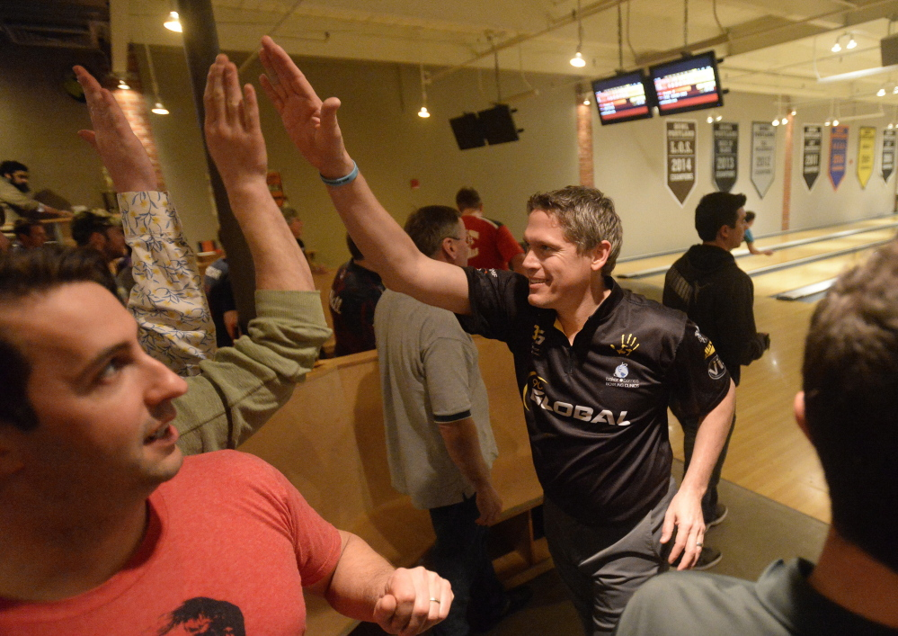 Chris Barnes of Texas gets a high-five after rolling a strike during the Professional Bowlers Association's Pro-Am on Thursday at Bayside Bowl in Portland. He's earned $2.5 million on the tour.