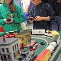 Oakland's Mary Wunderlich, left, and Jackson Small of Cumberland use remotes to control trains during the Maine3Railers Model Railroad Club's show on Saturday. Small's father, Dan Small, watches at right.