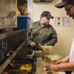 During a recent visit, food safety inspector Tom Williams, left, scrutinizes the food storage practices at Becky's Diner in Portland as Michael Sajecki, a line cook at the Commercial Street eatery, slices mushrooms for omelets. Partnering with restaurant owners, the city has dramatically improved its inspection program.