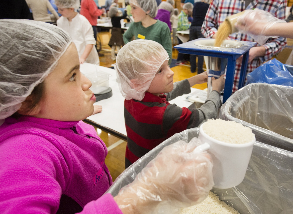 Volunteer Roxie Van Oosterun, 9, of Portland, left, awaits her turn to pour rice into a meal pack while Elias Bennett, 8, of Gray, holds a bag for filling beneath a funnel. The effort at Deering High School was organized by Million Meals Maine, a nonprofit started last year.