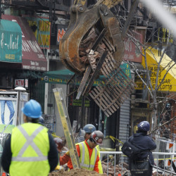 Debris are cleaned up from the site of a building collapse in the East Village neighborhood of New York, on Friday. A body was found Sunday in the rubble left behind by an apparent gas explosion.