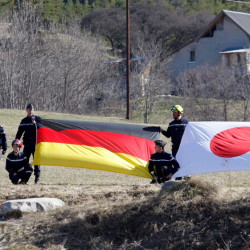 The German, left, and Japanese flags are displayed during a ceremony with family members of Japanese victims in the area where the Germanwings jetliner crashed in the French Alps, in Le Vernet, France, on Sunday.