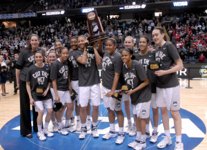 Connecticut players pose with the trophy after their 91-70 win over Dayton in a regional final Monday in Albany, N.Y.