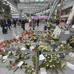 Passengers watch candles and flowers for the victims of the plane crash at the airport in Dusseldorf , Germany, Tuesday.