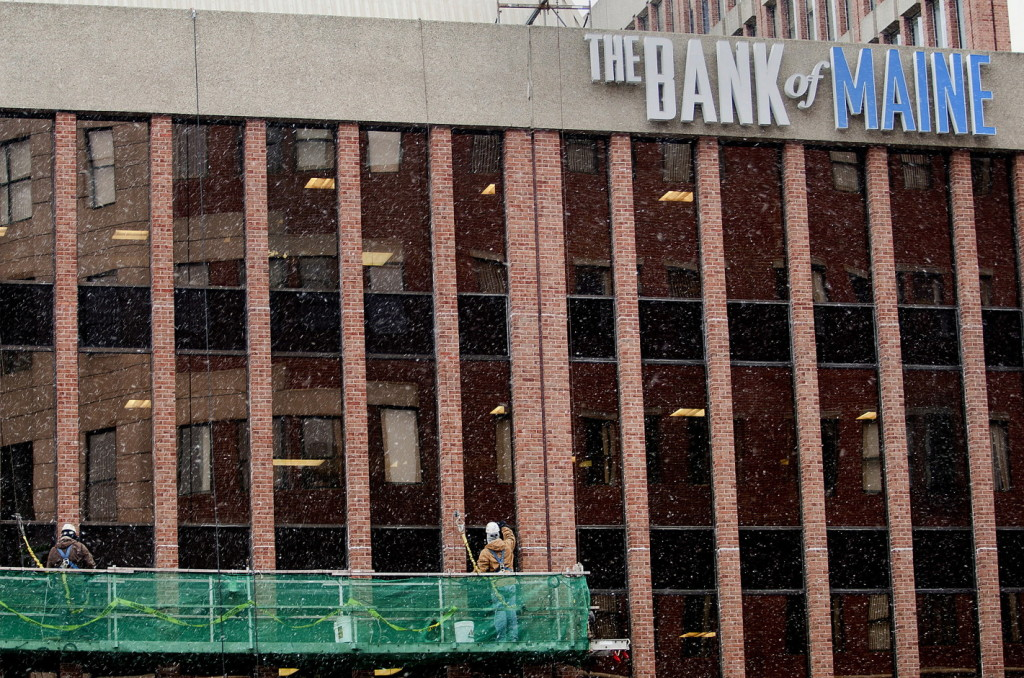 Workers clean the windows on the side of The Bank of Maine building in downtown Portland on Monday. The bank will be merging with Camden National Bank.