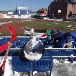 Workers at Hadlock Field remove snow in preparation for the Portland Sea Dogs' season opener on April 9. The team has guaranteed the game will be played, or fans will receive two tickets to a future game instead of the usual one. Courtesy of Portland Sea Dogs
