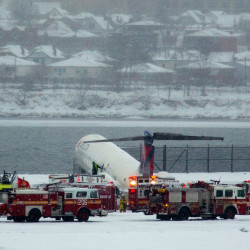 A Delta plane rests on a berm near the water at LaGuardia Airport in New York on Thursday,. Delta Flight 1086, carrying 125 passengers and five crew members, veered off the runway at around 11:10 a.m., authorities said.