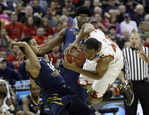 Maryland's Dez Wells, right, collides with West Virginia's Gary Browne, left, and Devin Williams during their game late Sunday night.