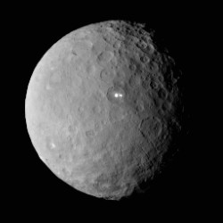As Dawn approached Ceres, it spotted a pair of puzzling bright spots inside a crater. Scientists think the shiny dots may be exposed ice or salt. This image was captured from a distance of nearly 29,000 miles. The dots are above and right of center. The Associated Press / NASA