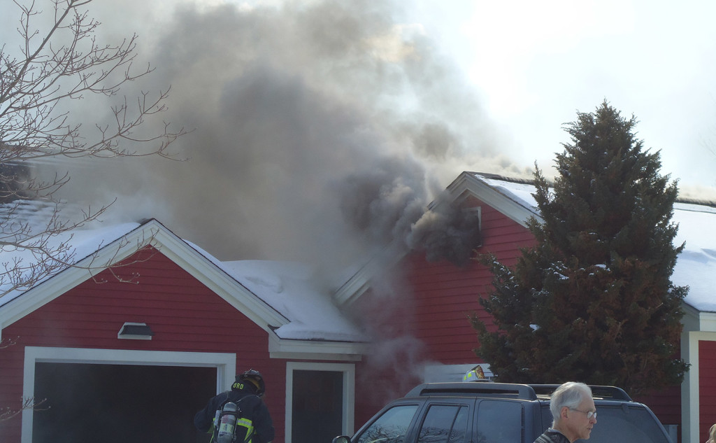 Smoke pours from the home at 146 Scott Dyer Road in Cape Elizabeth on Monday. Fire officials blamed snow and ice for severing a propane line, which fueled an explosion and fire.