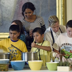 First lady Michelle Obama watches as school children prepare lunch in the East Room of the White House following the annual fall harvest of the White House Kitchen Garden in October 2014. The first lady is challenging the nation''s children to dream up healthy lunch recipes, a now annual component of her Let''s Move! campaign to reduce childhood obesity through diet and exercise.