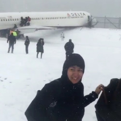 In this image taken from video provided by passenger Larry Donnell, a New York Giants NFL football player, passengers are evacuated after a Delta plane skidded off the runway at LaGuardia Airport during a snowstorm Thursday in New York.
