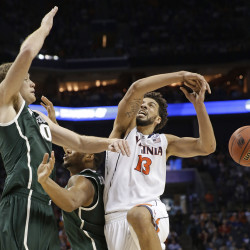 Michigan State's Matt Costello, left, knocks the ball from Virginia's Anthony Gill, right, during the second half of an NCAA tournament college basketball game in the Round of 32 in Charlotte, N.C., Sunday. The Associated Press