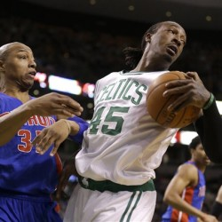 Detroit Pistons forward Caron Butler and Boston Celtics forward Gerald Wallace grapple over a loose ball in the second quarter Sunday in Boston. The Associated Press