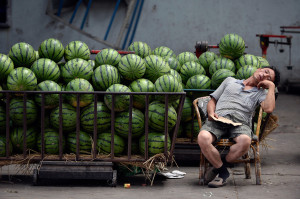 A vendor selling watermelons naps as he waits for customers at a market in Taiyuan, Shanxi province, China.