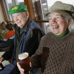 Betty Pomroy of Portland and Robert Earles of South Portland watch Irish dancing at Ri Ra Irish Pub and Restaurant in Portland after Sunday's annual St. Patrick's Day parade. About 80 people participated in the parade despite a chilly, wind-blown rain. 2010 Press Herald File Photo/Derek Davis