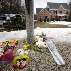 A memorial appears Monday in front of a home in Bedford, N.H. The Associated Press
