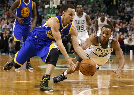 Golden State Warriors guard Stephen Curry beats Boston Celtics guard Avery Bradley to a loose ball in the second half of the Warriors' 106-101 win in Boston on Sunday. The Associated Press