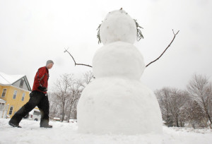 Nate Ruel carries rocks to be used as eyes and buttons on a 7-foot tall snowman he built along Day Street in Kennebunk on April 1, 2011. The heavy, wet snow on made for good snowman building but also hard shoveling.
