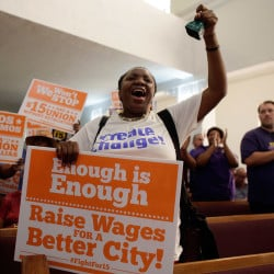Activist Paulette Darow rings a cow bell Wednesday as protesters listen to speeches at the Greater Bethel AME Church in Miami in support of raising the minimum wage to $15 an hour as part of an expanding national movement. The Associated Press