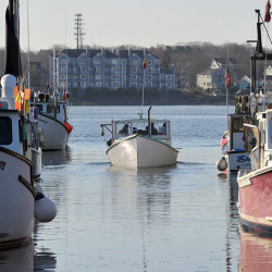 A fisherman backs his boat out into Portland Harbor framed by lobster boats tied up at Widgery Wharf, left, and Union Wharf in Portland.