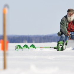 "Ervin Lizotte of Lebanon keeps an eye on a trap in the foreground as he jigs for togue from his vantage point on Sebago Lake in Standish on Sunday. ""There is not a lot of noise on the lake right now,"" he says, adding that he'll keep fishing as long as he can."