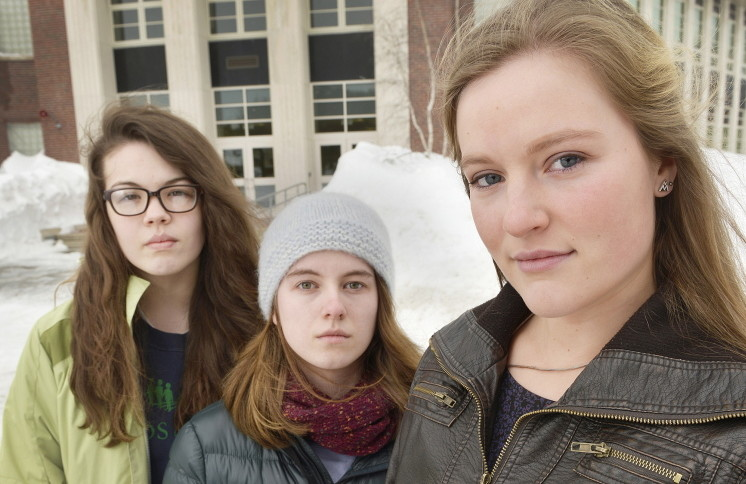 In this February 2015 file photo, South Portland senior class President Lily SanGiovanni, right, joined by two of her supporters, Morrigan Turner, left, and Gaby Ferrell, stand in front of the high school where she led an effort to let students and teachers know they don't have to say the Pledge of Allegiance.