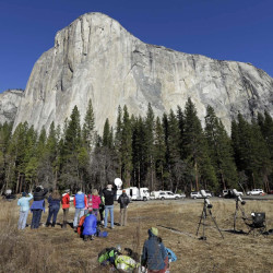 Spectators gaze at El Capitan in Yosemite National Park in California, where fees will increase this summer.