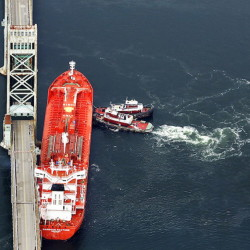 Seen in this aerial photograph, tugboats hold the Harbour Feature in place against the Sarah Mildred Long Bridge after it slipped off its mooring at the New Hampshire State Pier on April 1, 2013. A new federal report says the ship's operator had failed to replace a component of the mooring system.
