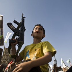 A boy holds a weapon Wednesday in Sanaa, Yemen, at a rally protesting Saudi-led airstrikes. The Associated Press