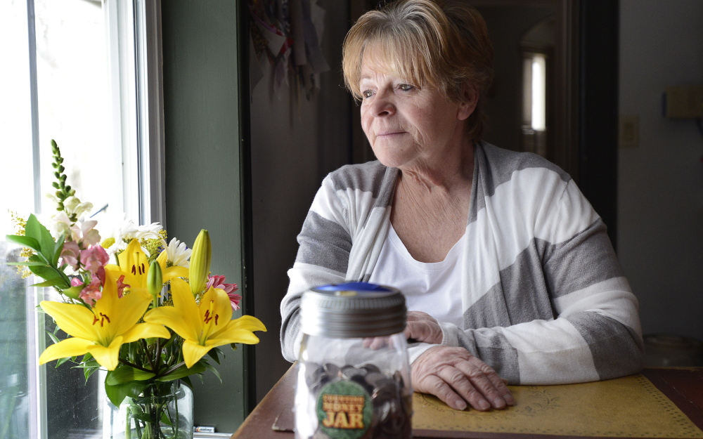 """I am embarrassed that I still smoke,"" says Linda Dennison, 64, of Baldwin, whose results from a Mercy Hospital CT scan came back negative for lung cancer. Newly determined to quit after the recent death of her brother, a heavy smoker, Dennison socks away coins in a jar, foreground, to show the money she saves from not smoking."