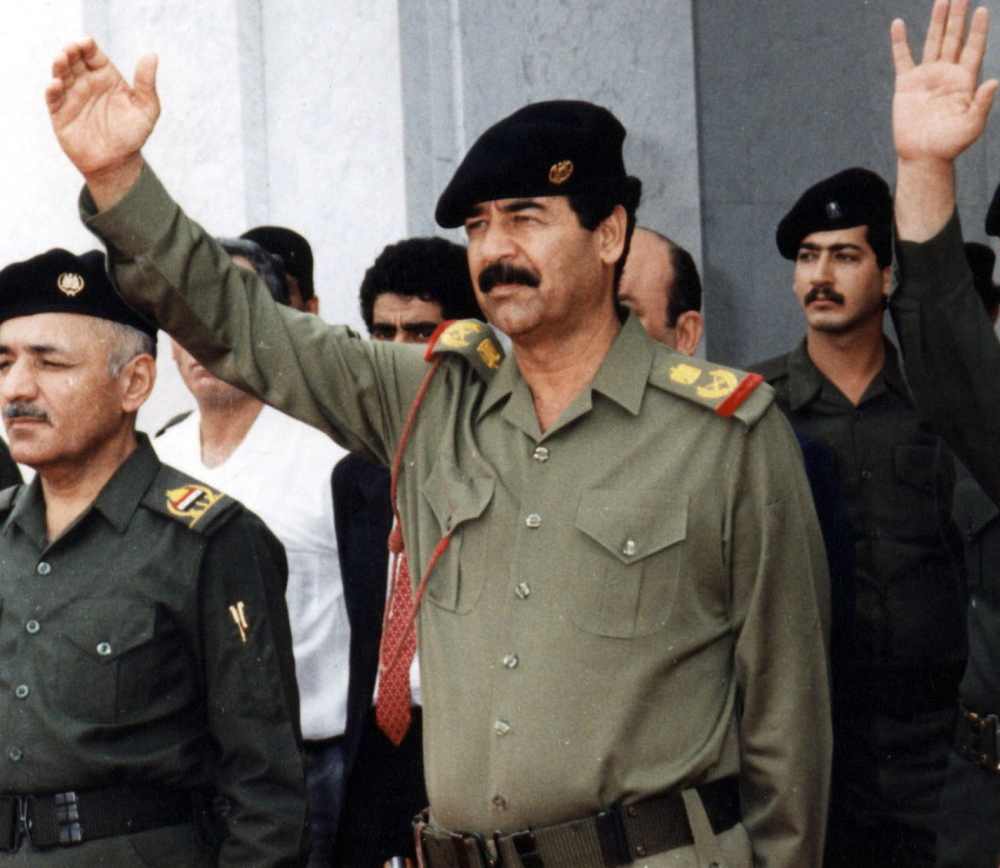 """Iraq's former dictator, Saddam Hussein, center, is shown in Baghdad in 2004. Apologists acknowledge that he perpetrated atrocities but chalk them up to clarivoyance, saying, """"Saddam knew what Iran wanted to do,"""" and praising him for understanding the enemy."""