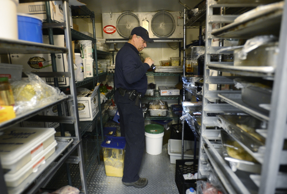 Scott Davis, a health inspector with the state of Maine, inspects a restaurant in York in 2013. The Legislature's Health and Human Services Committee is scheduled to hold a public hearing Monday on a bill to increase the number of health inspectors, with a goal of reaching all restaurants on an annual basis.