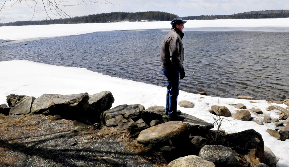 Tim Comeford checks the amount of ice on Long Pond in Belgrade on Sunday. Comeford said the lake's ice usually is all gone by the third week of April.