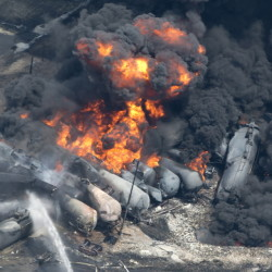 Smoke and flames billow from derailed railway cars carrying crude oil in downtown Lac-Megantic, Quebec, on July 6, 2013. Families of the 47 people killed in the disaster stand to split nearly $86 million as compensation.