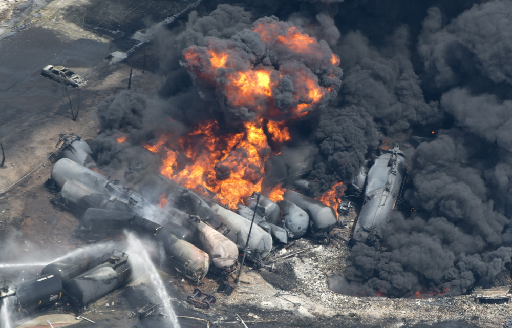 Smoke and flames billow from derailed railway cars carrying crude oil in downtown Lac-Megantic, Quebec, on July 6, 2013.
