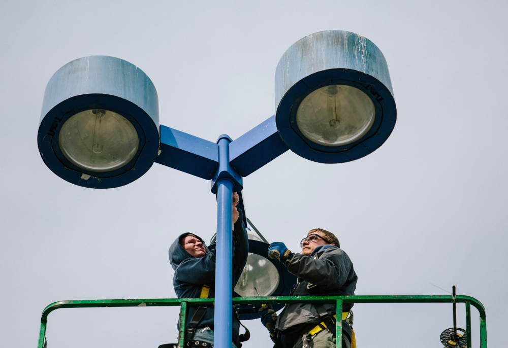 Seabee Electric employees Madison Hanson, left, and Nick Dyro install LED lights in The Maine Mall parking lot in South Portland on Wednesday. The LED lights will use one-third to one-half less power than the old lights.