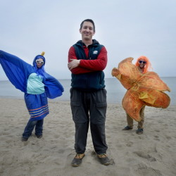 Drew Dumsch, center, executive director of The Ecology School, along with staff members Haley Diamond, left, dressed as a great blue heron, and Aaron Altabet, dressed as a sea star, at the beach near the school in Saco.