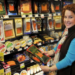 Kasey Harris, sustainability specialist at Hannaford, checks over seafood prodcuts at the market.