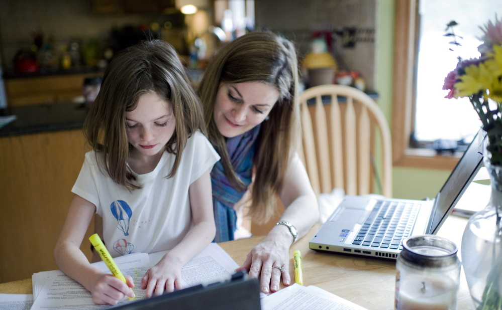 Kelly Howard works with her 7-year-old daughter Zoey, who has dyslexia, at their home in New Hartford, Conn. Legislation that went into effect in January adds a checkbox for dyslexia under students' individualized education plans, a step parents say will help schools focus on the disorder.