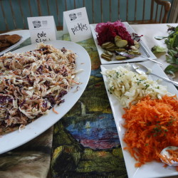 "The upscale spread includes cole slaw, pickles and greens at a bean ""suppah"" prepared by Rosemont Market's Brad Messier last month at the Deering Grange in Portland."
