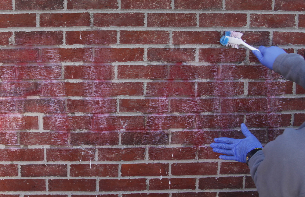 Hanad Nur, an employee at the Portland Halaal Market, uses paint stripper to remove offensive graffiti from the side of the business Sunday.  Jill Brady/Staff Photographer