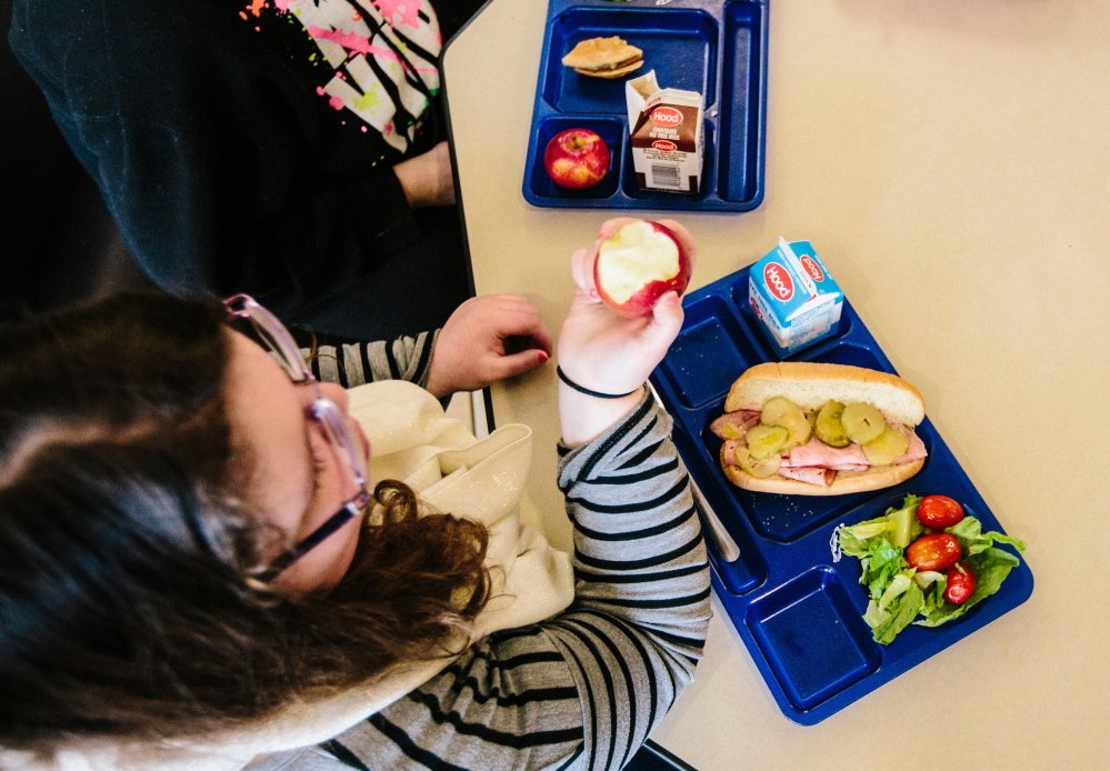 Seventh-grader Hailey Remington bites into an apple. Cafeterias across Maine are shifting away from institutional food, with whole wheat, dark green vegetables and fruit on school menus more often. Whitney Hayward / Staff Photographer