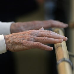 A senior keeps her hands close the the handrail as she works on her balance exercises in the U-ExCEL fitness program at Piper Shores in Scarborough. The best advice for keeping your brain sharp is to keep physically active.